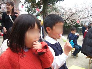 演奏や人形劇に見入りながら団子を食べる@幼稚園の桜祭り
